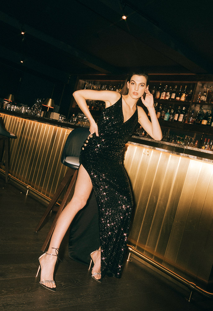 Photograph of a female model wearing a Balmain sequin strap dress, Saint Laurent YSL earrings, Gianvito Rossi Camnero crystal strap stilettos, and Tom Ford small Oalmellato triple chain bag