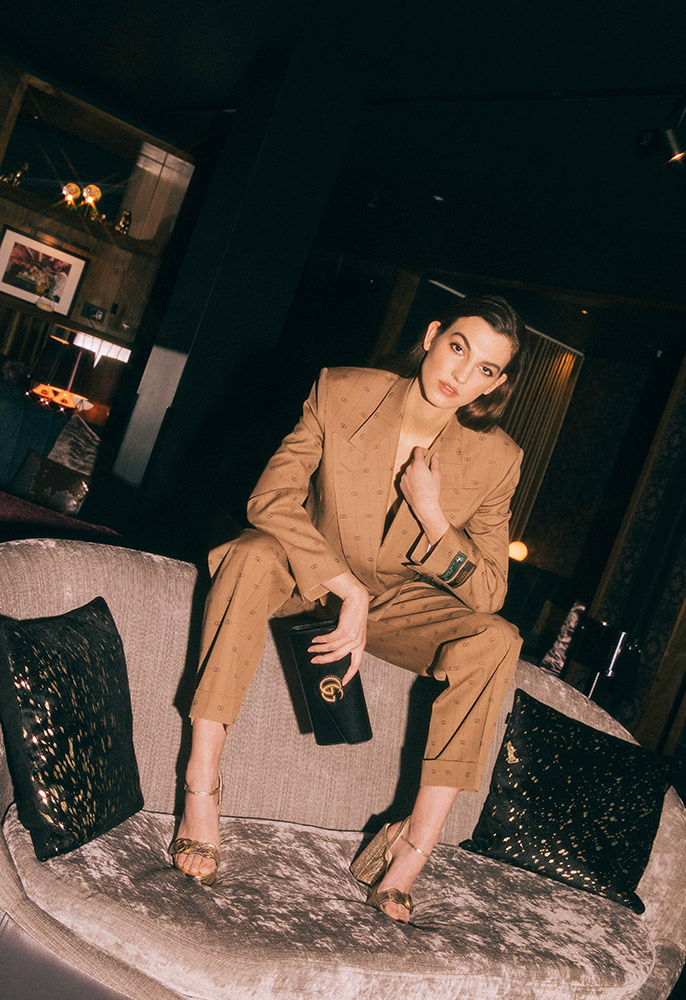 Photograph of a female model wearing a Gucci retro GG blazer and trousers, platform sandals, and Broadway clutch bag