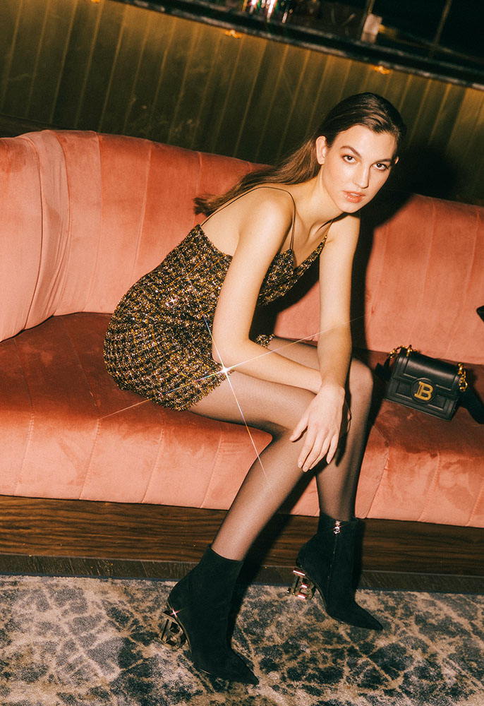 Photograph of a female model wearing a Balmain short sequin dress, sequin tweed suit jacket, Nicole B boots and calf leather B bag