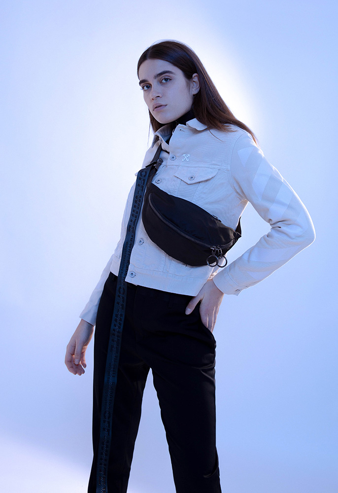 A female model wearing a black Off-White matching track top and bottoms with a yellow Off-White denim jacket layered over the top printed with the Off-White diagonal stripes and arrow logo