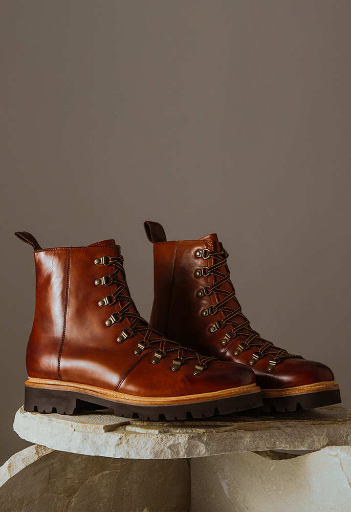 A pair of brown leather lace-up Grenson hiking-inspired boots with brushed metal eyelets and a solid sole
