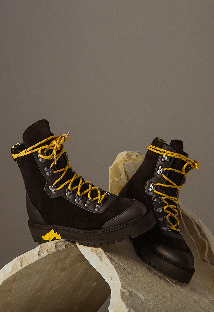 A pair of black Off=White hiking lace up boots with yellow laces and details