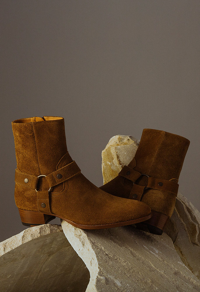 A pair of brown suede Saint Laurent Wyatt Western-style boots with brushed bronze harness straps and a block heel