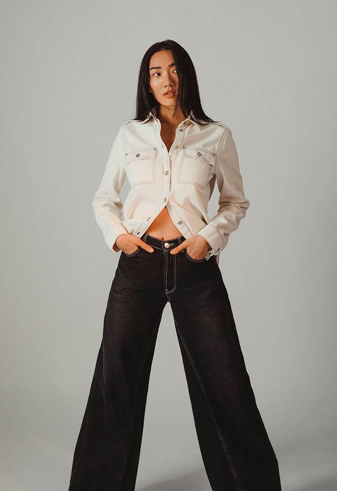A woman stood up with her hands in her jeans pockets wearing a white denim shirt and black flared Ganni jeans with an exposed midriff