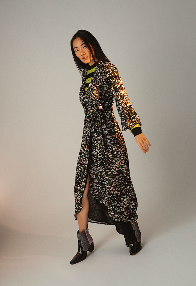 A woman wearing black leather Western amkle boots with bare legs, a long sleeved maxi dress in a floral print with a V kneckline and wraparound layered over a green and black striped knit