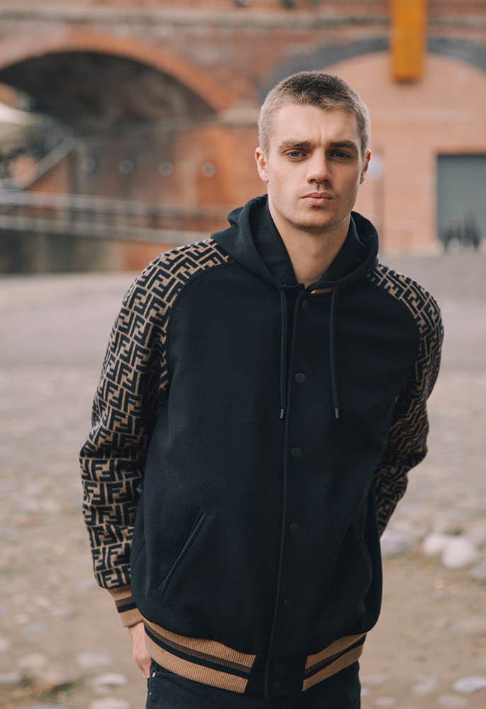Photograph of a male model wearing a black and brown wool blend Fendi bomber jacket with a double F logo printed sleeve