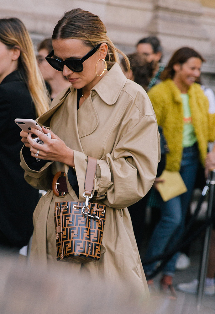 Street style photograph of a woman wearing a camel coloured trench coat and brown Fendi leather bag