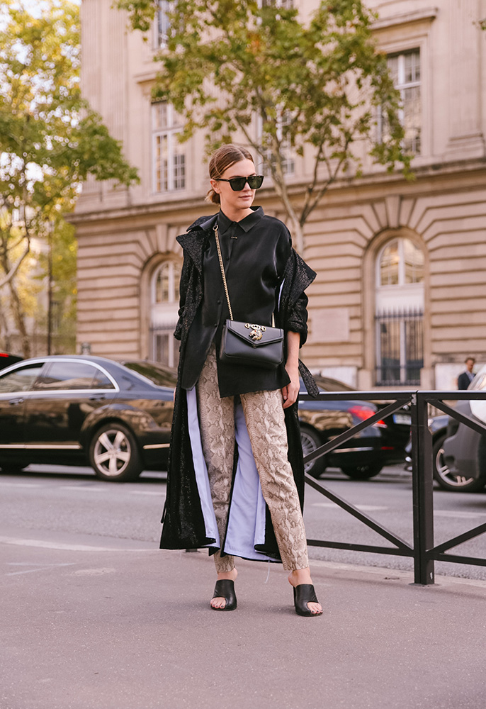 Street style photo of a woman wearing a pair of snakeskin trousers, black boots and a leather Gucci bag with a diamante tiger head