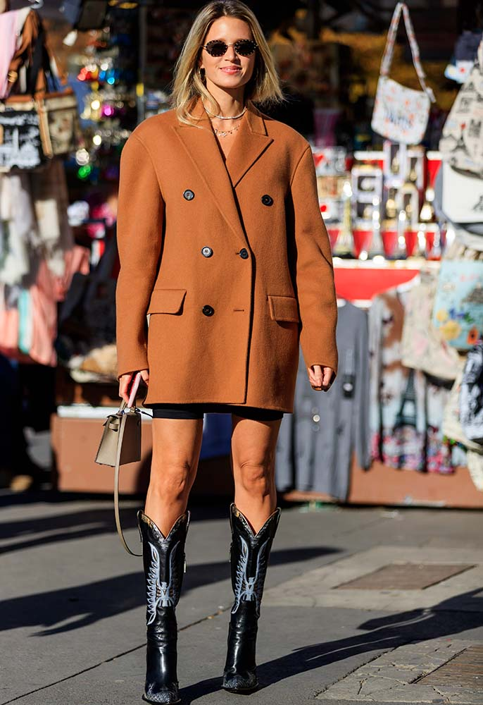Street style photo of a woman wearing an oversized brown blazer and brown leather cowboy boots