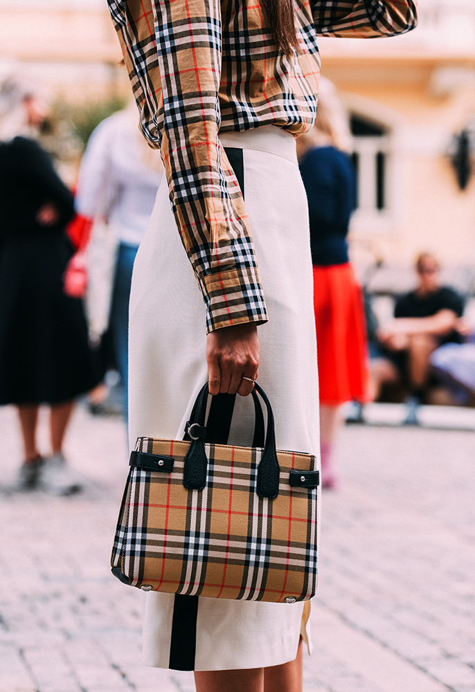 Street style photo of a woman wearing a Burberry checked shirt, white skirt and Burberry checked bag