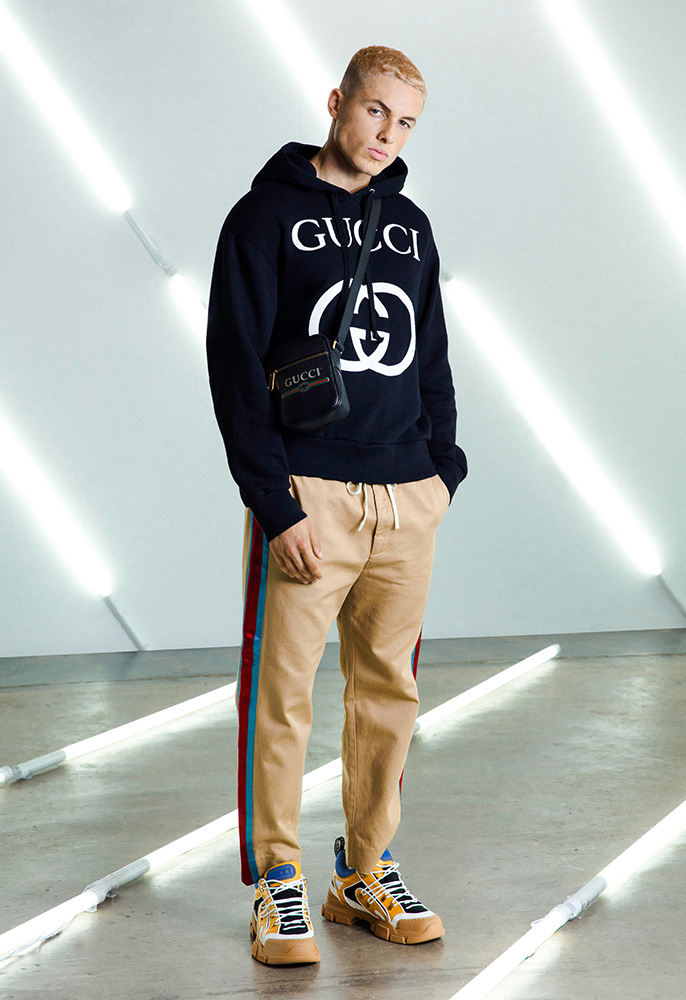 A male model wearing a black Gucci hooded sweatshirt with a white Gucci GG logo on it, beige Gucci trousers with red and blue side stripes and chunky Gucci yellow and blue Flashtreck trainers