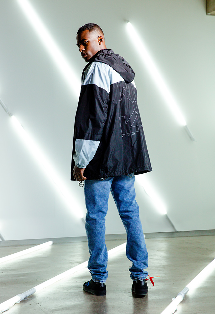 A male model wearing a blue and black off-White rain coat over a logo Off-White denim jacket with distressed blue Off-White jeans and black low top Off-White 2.0 trainers with an orange tag