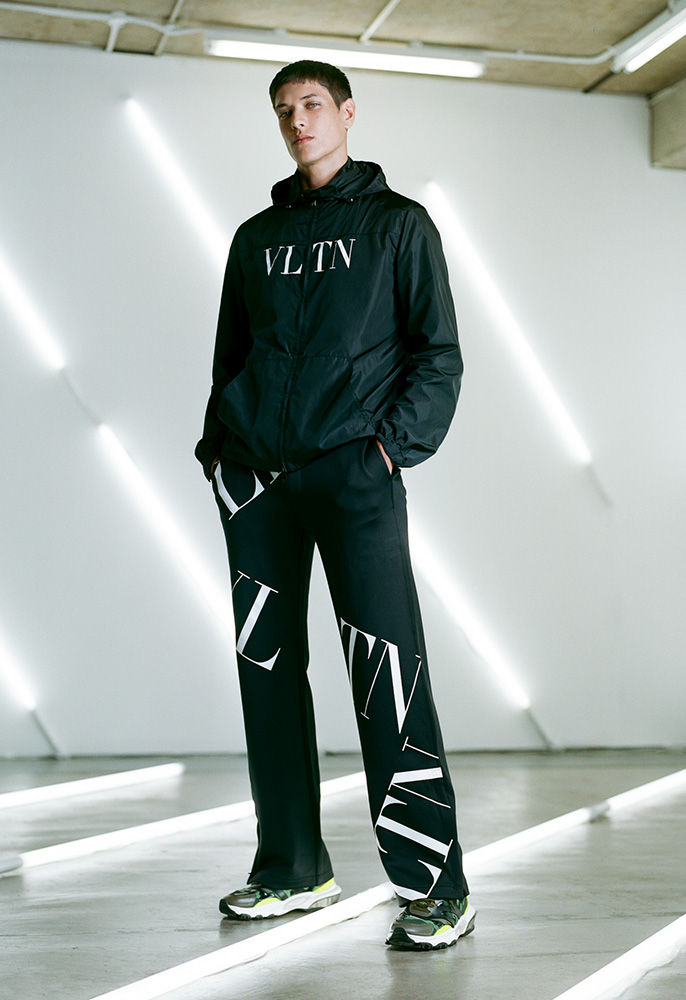A male model wearing a black zip up VAlentino track top with a white VLTN logo, black Valentino track pants with all over VLTN logos and green camo mesh Valentino Bounce chunky trainers