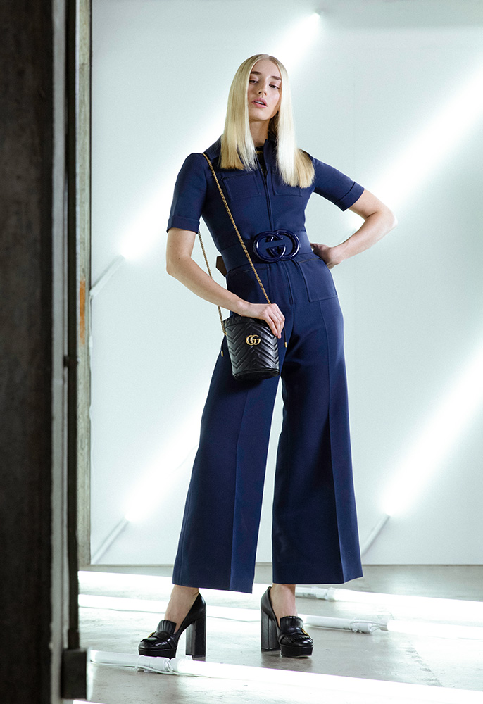 A female model wearing a navy blue wide legged Gucci jump suit with cropped sleeves and a GG belt with Gucci tassle loafer platforms and a black leather Gucci matelasse bucket bag