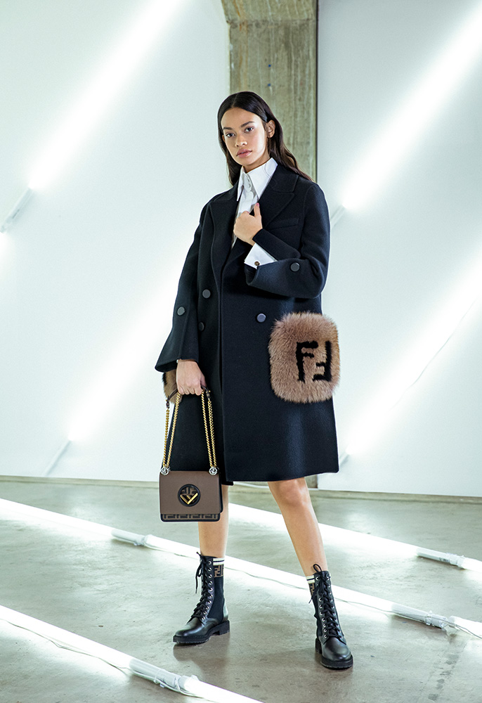 A female model wearing a Fendi mid length coat with fur FF pockets, a white bow neck blouse, a beige Fendi mini skirt, Fendi combat boots and a Fendi logo bag