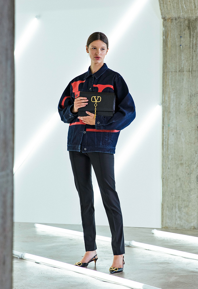 A female model wearing an oversized Valentino logo denim jacket with black Valentino cigarette pants, black Valentino kitten heel pumps with pointed toes and gold V logos and a Valentino shoulder bag