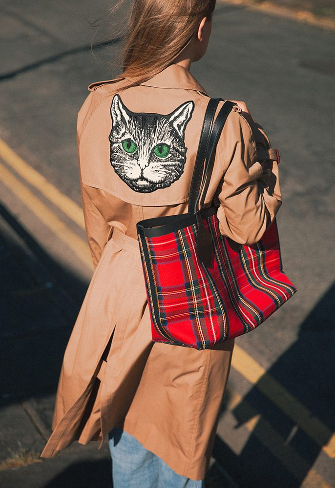 Female model wearing a Gucci trench coat with a beaded cat applique on the back, Burberry jeans, a red check Burberry bag and black fringed Gucci shoes