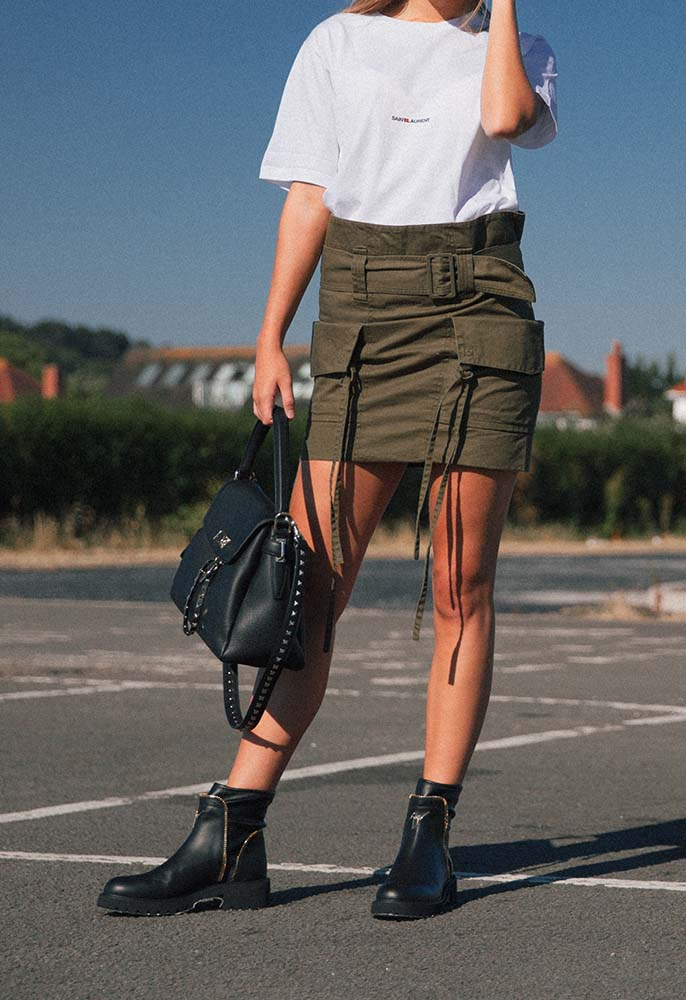 Female model wearing a military-inspired Saint Laurent mini skirt, chunky black leather boots, Saint Laurent white T-shirt and Valentino Rockstud bag