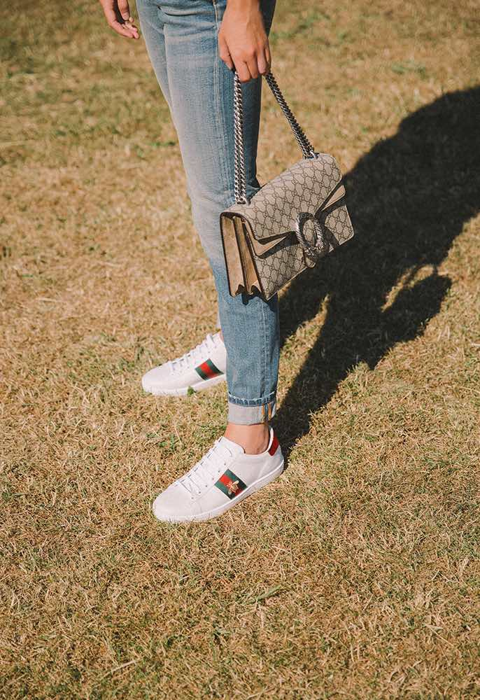 Model wearing a pair of Saint Laurent blue faded jeans, Gucci Dionysus bag and Gucci web strip embroidered-bee trainers