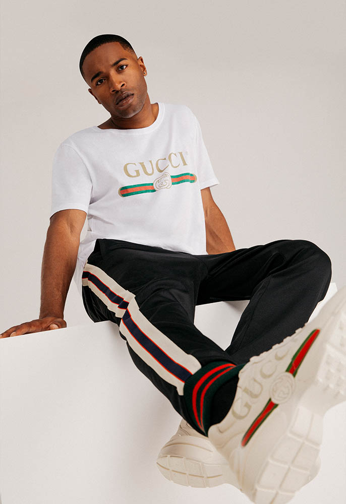 A male model wearing a white Gucci logo Tee, side-stripe Gucci tracksuit bottoms and chunky Gucci logo Rhyton trainers