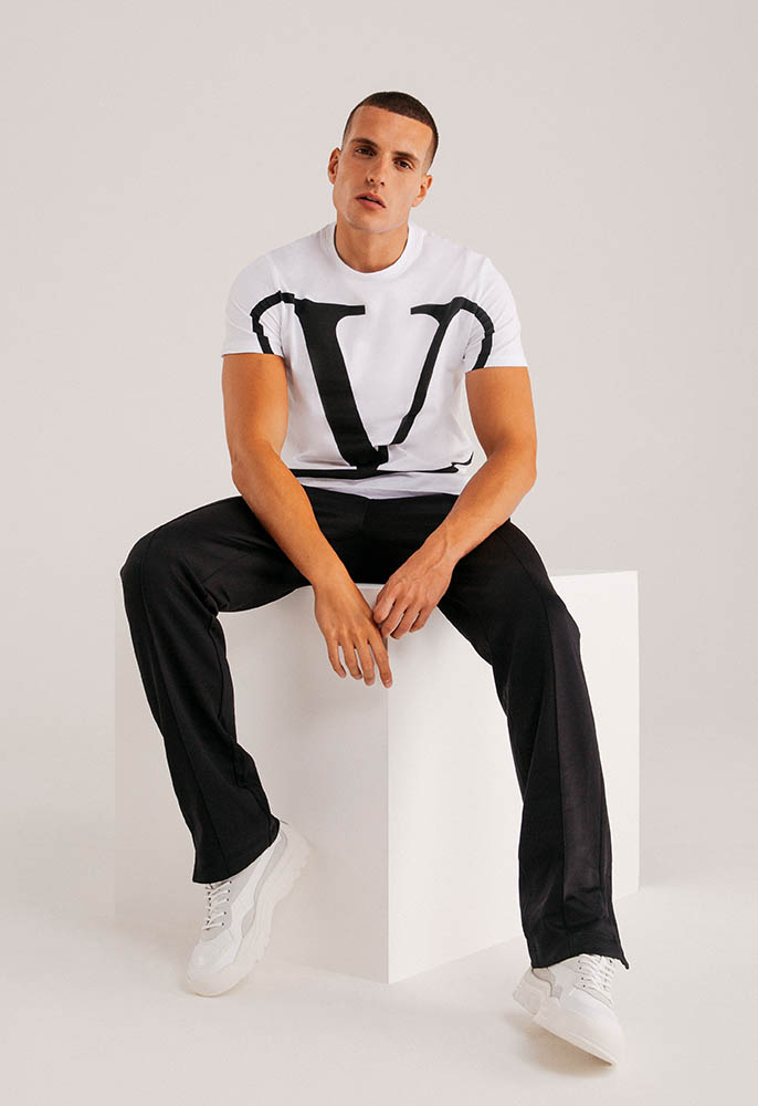 A male model wearing a white Valentino T-shirt with a large black V logo graphic, plain black Valentino studded jogging bottoms and white Valentino trainers