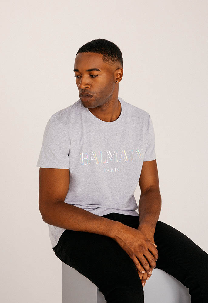 A male model wearing a marl grey logo Balmain T-shirt with an irridescent metallic logo, and black jeans