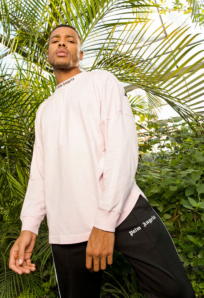 A male model stood in front of palm trees and shrubs in a butterfly house, wearing a pale pink Palm Angels long-sleeved jersey logo top and black Palm Angels track pants with white side stripe and logo