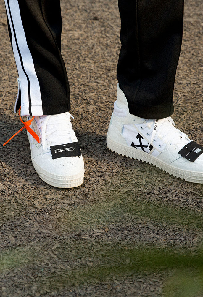 A photograph of a male model's feet wearing black and white Off-White high top trainers with white laces and the brands orange industrial tag