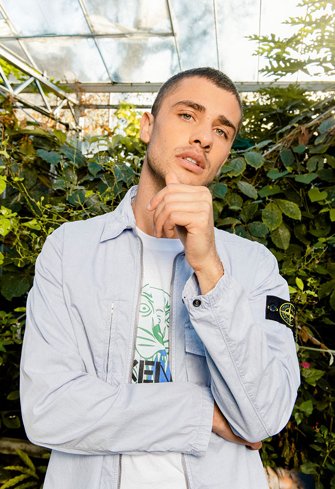 A male model stood in front of palm trees and shrubs in a butterfly house, wearing a lilac Stone Island overshirt with compass patch on the arm and a white Kenzo Tiger T-shirt underneath