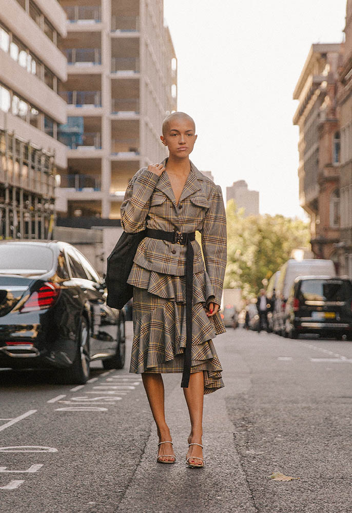 A woman stood on the street outside the London Fashion Week shows wearing a checked belted blazer and matching ruffle-hem midi-skirt