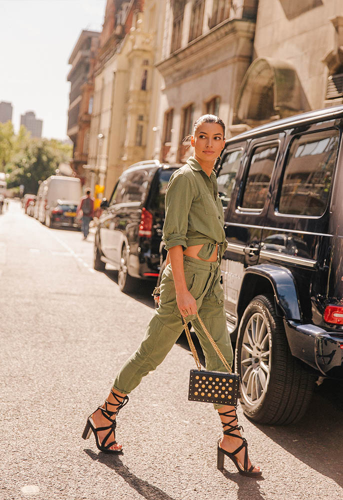 A woman in the street at London Fashion Week wearing a khaki safari jacket and trousers, black strappy heels and a gold and silver studded bag