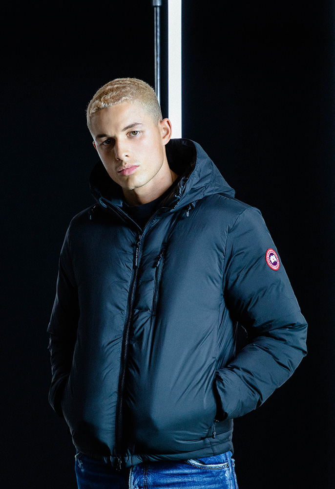 A male model wearing a dark navy blue hip-length Canada Goose padded down jacket with a hood and the Canada Goose circular badge on the arm