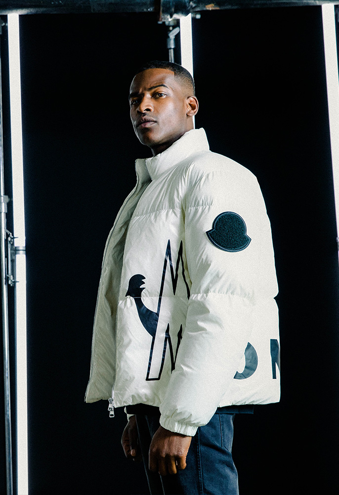 A male model wearing a white and black Moncler jacket with the Moncler logo printed across the bottom of the jacket hem in large graphic writing