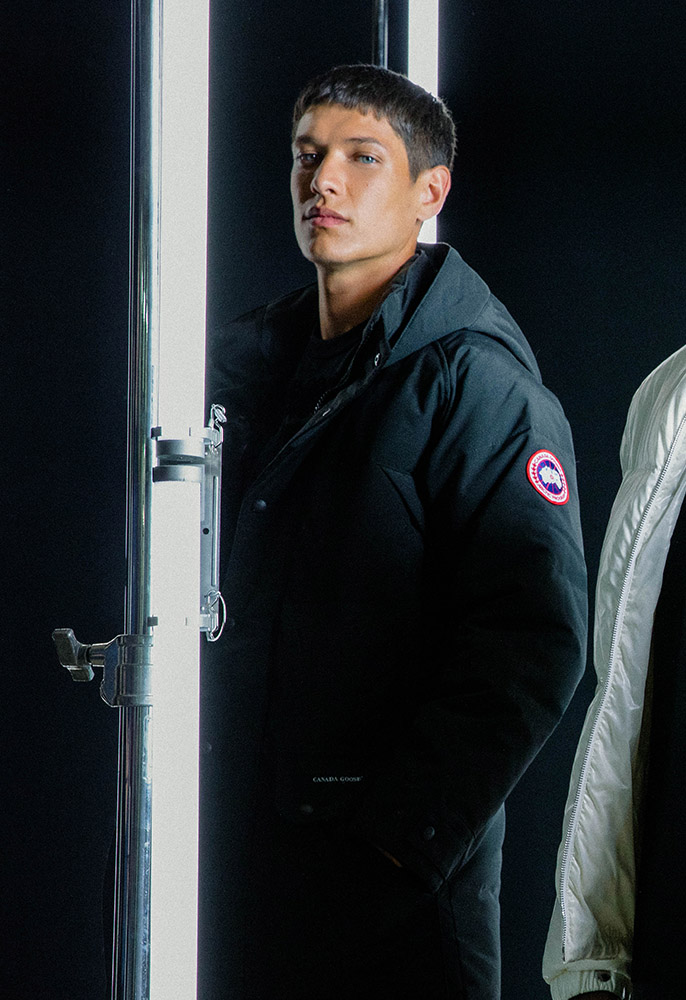 A male model wearing a black Canada Goose Emory thigh length parka with a hood and the trademark Canada Goose logo patch on the arm