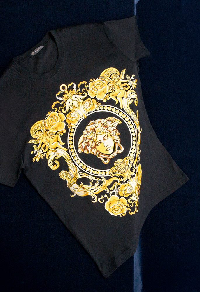 A black Versace T-shirt with a gold foiled Versace baroque face