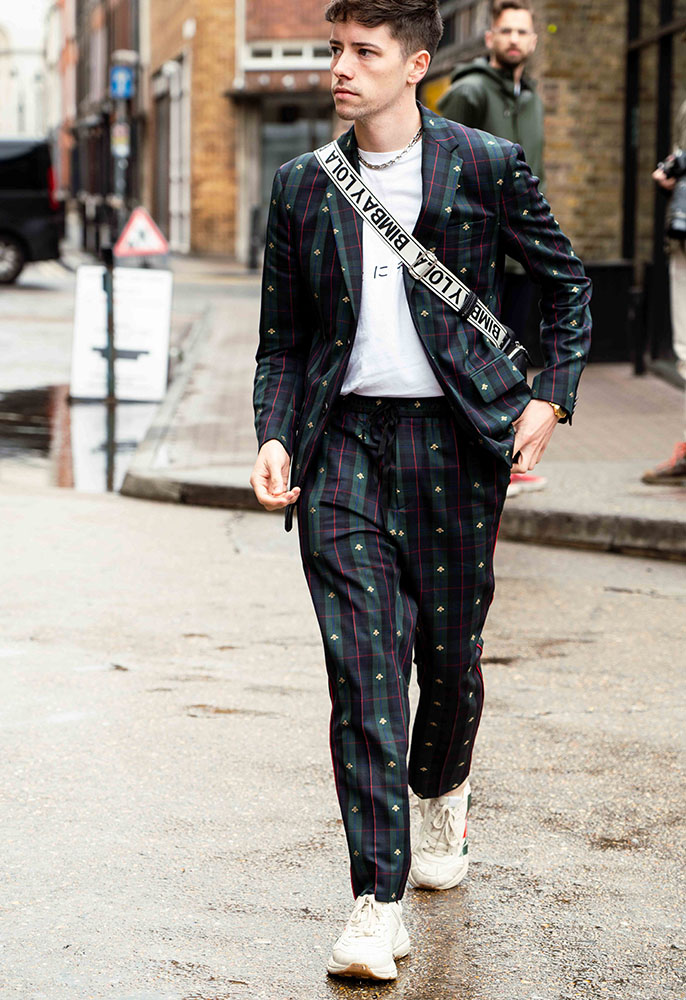 A London Fashion Week men's attendee wearing an embroidered Gucci two-piece suit, a white T-shirt and white chunky Gucci trainers