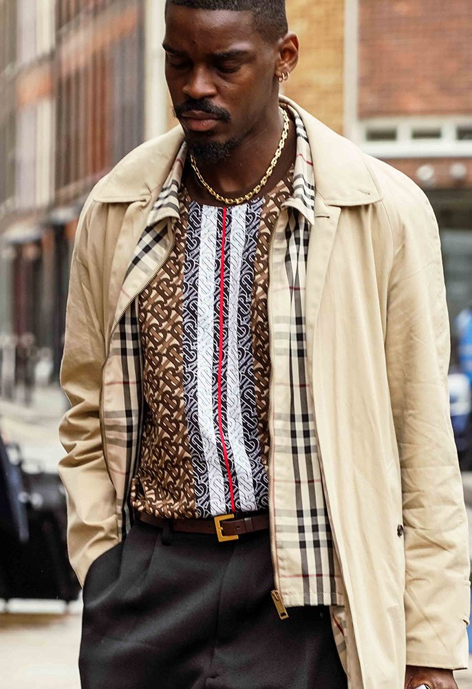 A guest at London Fashion Week Men's wearing a Burberry trench with a check layered lining, a Burberry monogram TB T-shirt, a pair of greay suit trousers and a gold chain necklace