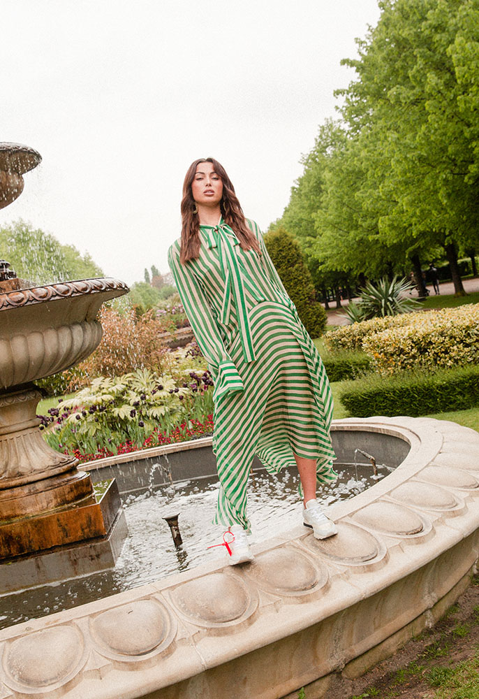 A female model stood in front of a water fountain in a green park wearing a green and white stripped sheer hanky hem silk dress by Petar Petrov and Off-White trainers