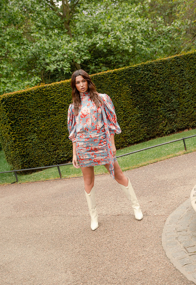 A female model stood in a park wearing a blue, red and cream floral print Magda Butrym mini dress with ruching, mid length blouse sleeves and a high necckline with a pussy bow back detail, with knee-high cream leather Magda Butrym heeled boots