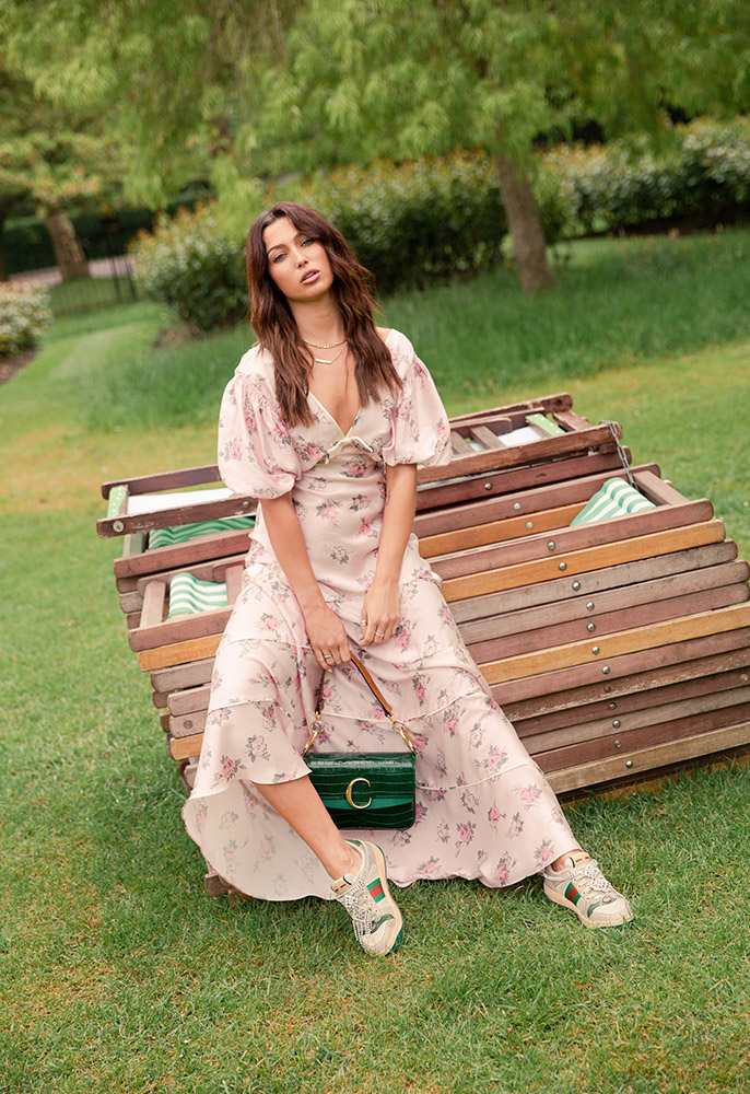 A female model in a park sat on a pile of green and white striped folded deck chairs, wearing a pink silk floral print LoveShackFancy maxi dress with puff sleeves and a V neckline with distressed Gucci trainers embellished with crystals and a green mock-crock Chloe top handle bag