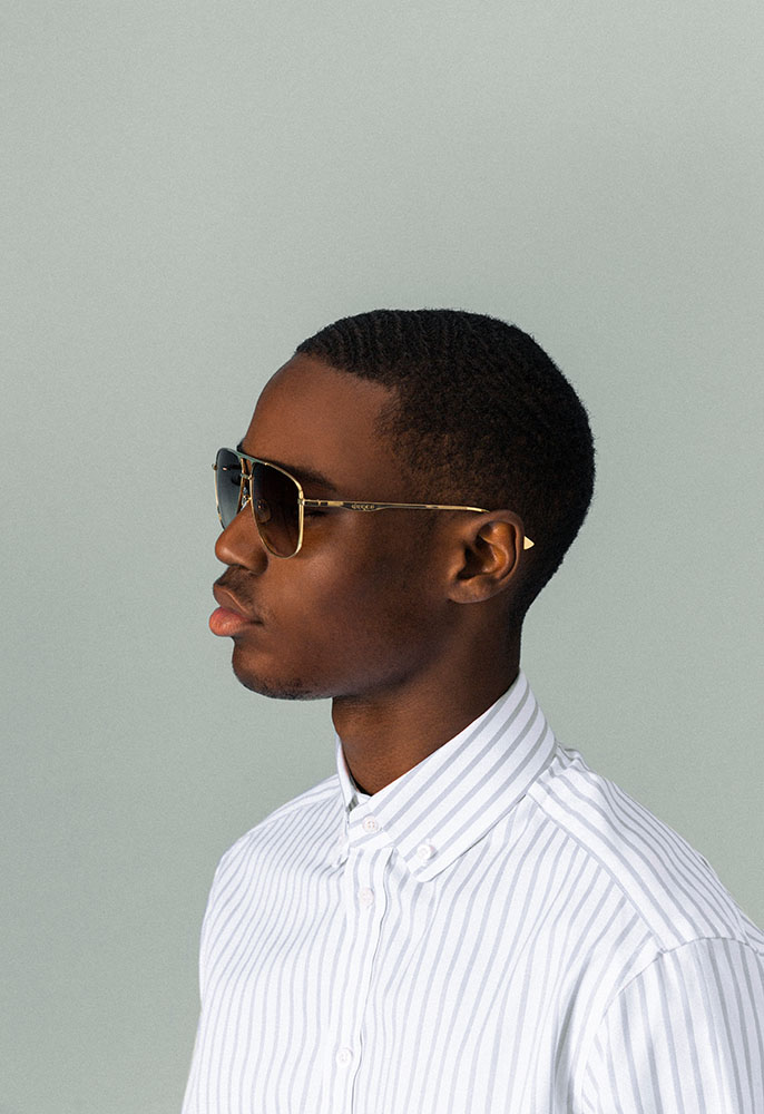 A head shot of a male model wearing a white and blue oversized Gucci striped shirt and a pair of gold framed Gucci sunglasses with a double brow bar and dark lenses