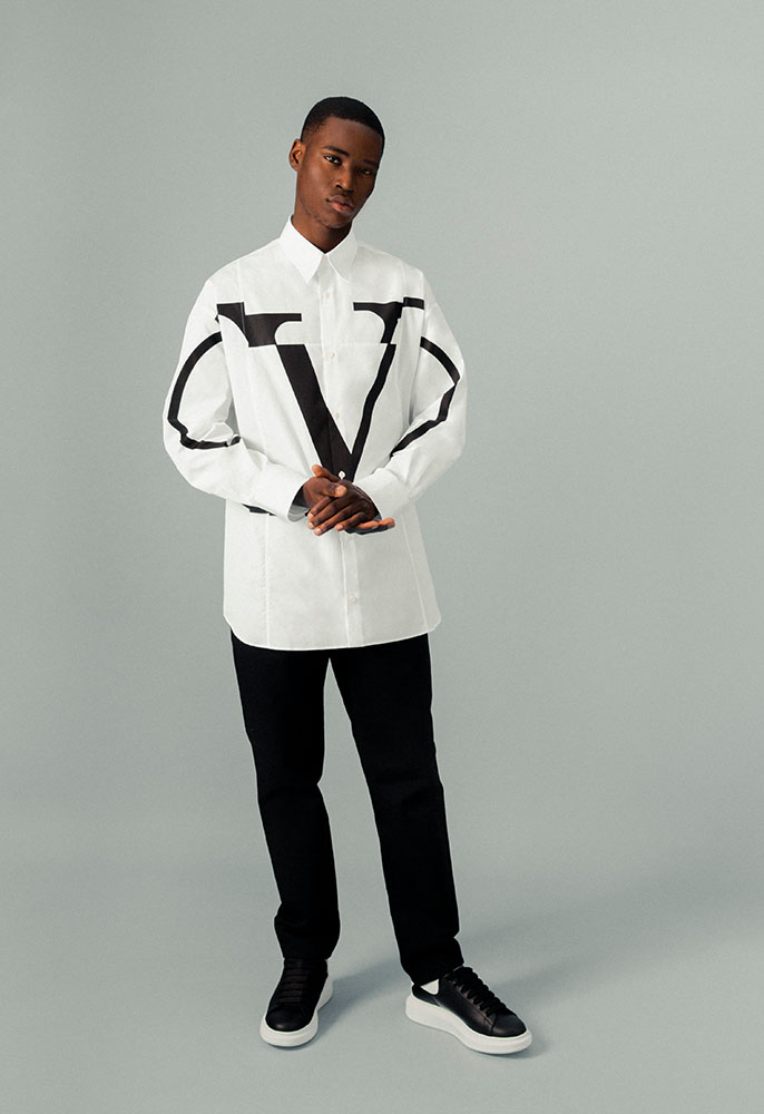 A male model wearing a white oversized Valentino shirt buttoned to the colar with a large black Valentino VLOGO graphic across the chest and sleeves, black Gucci cargo pants and black oversized Alexander McQueen trainers.