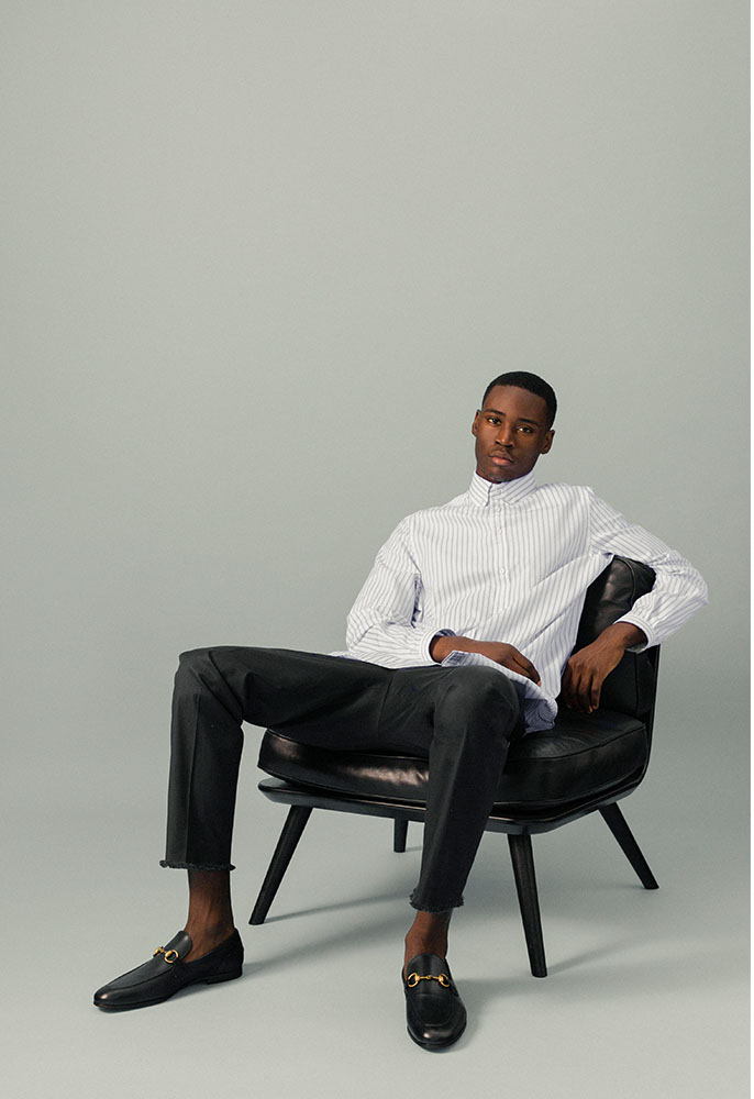 A male model sat on a leather chair wearing a blue and white stripe oversized Gucci shirt buttoned to the neck, black Neil Barratt trousers with frayed hems and black Gucci horsebit loafers