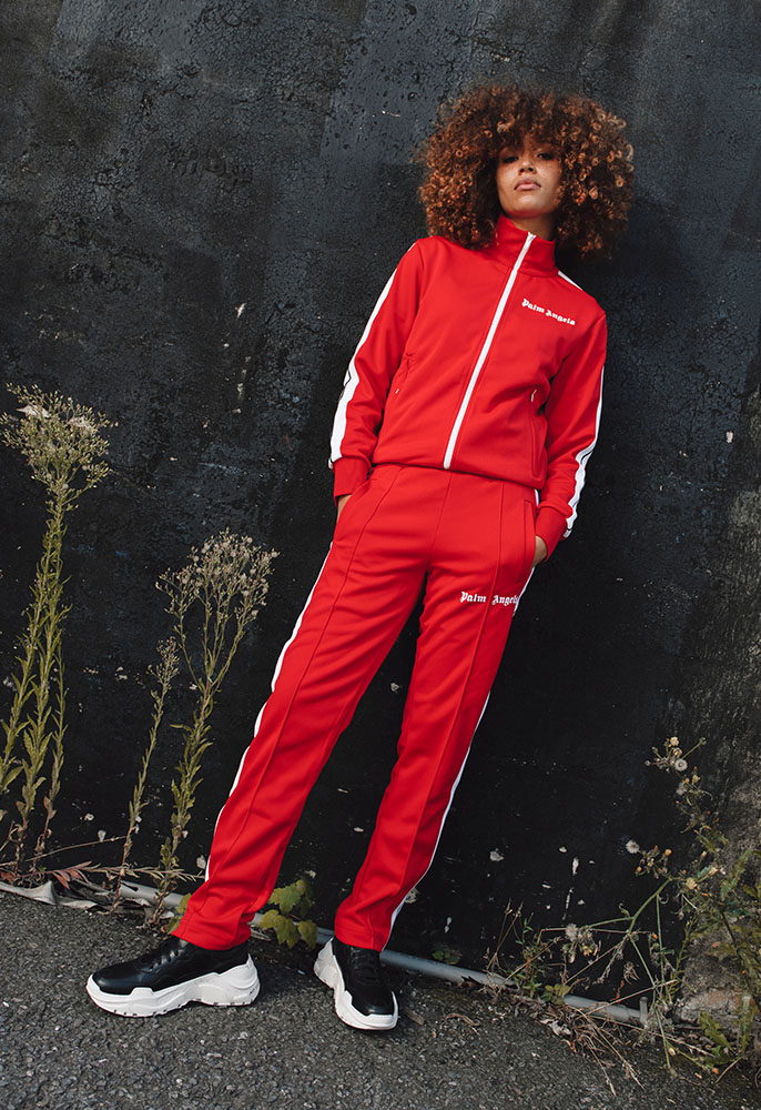 Photograph of a female model wearing a red two piece Palm Angels tracksuit and black Philipp Plein trainers with a chunky white sole