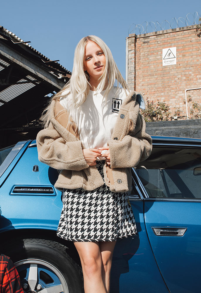 Photograph of a female model wearing an Off-White teddy bear jacket, Off-White houndstooth and T-shirt and black Giuseppe Zanotti trainers