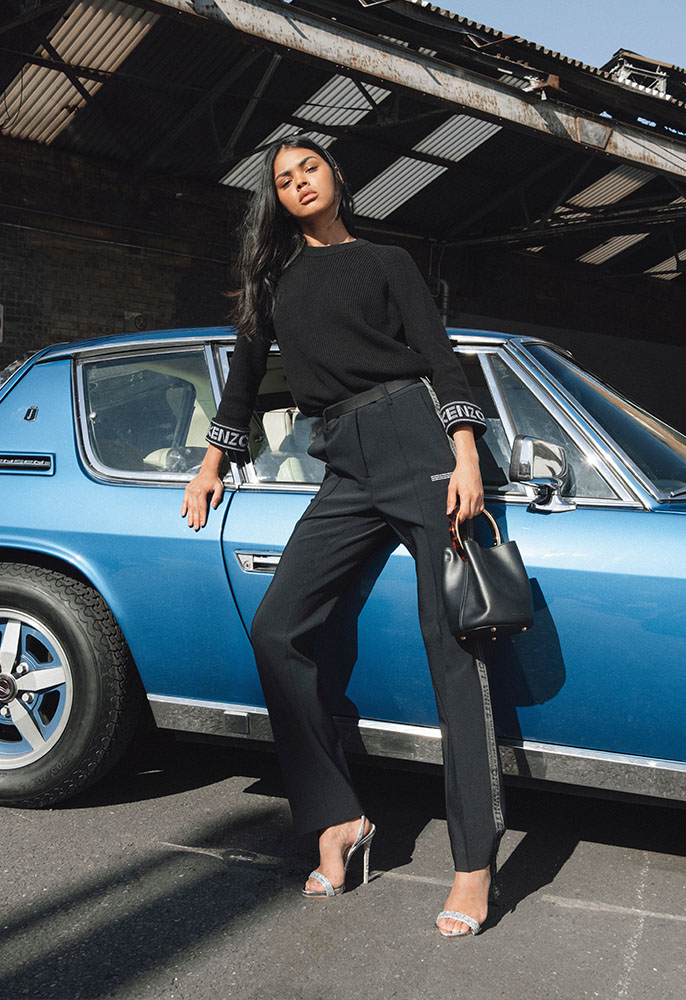 Photograph of a female model next to a vintage car wearing black Off-White track pants, a Kenzo knit and black leahter Marni bag