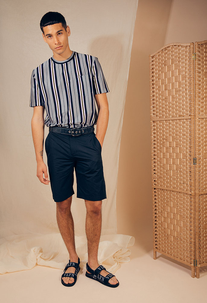 A male model wearing a striped navy, grey and white Lanvin T-shirt, a pair of loose-fit navy shorts, a navy Fendi logo belt and black Valentino sandals with velcro straps and white VLTN logos