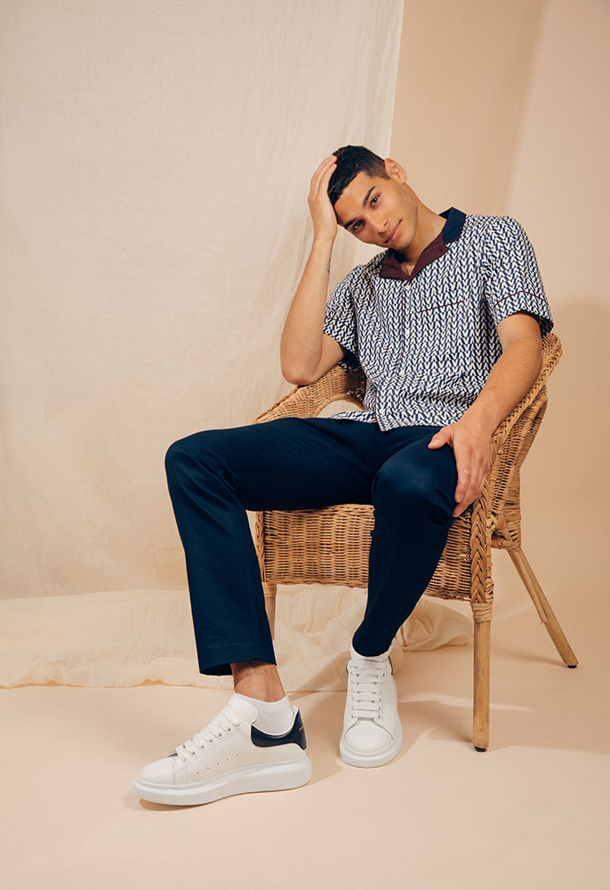 A male model sat on a wicker chair wearing a navy, white and burgundy camp collar Valentino shirt in an optical print with navy Gucci chinos and white oversized Alecander McQueen trainers