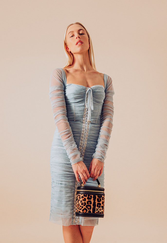 A woman wearing a pale blue Dolce & Gabbana midi dress with a ruched corseted bodice, a sweetheart neckline with long transparent sleeves and a pony skin Dolce & Gabbana leopard print handbag in the shape of a small vanity case