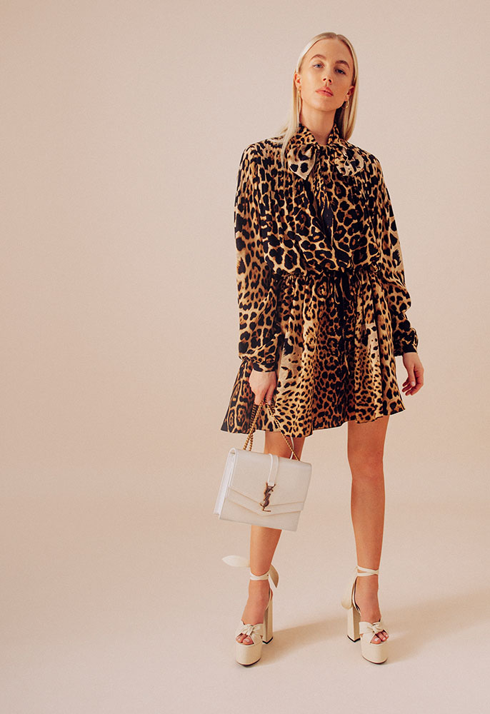 A woman wearing a leopard print Saint Laurent mini dress with a flared skirt, pussy bow neckline and long blouson sleeves, cream leather Saint Laurent platform sandals and a cream leather Saint Laurent bag with a YSL logo